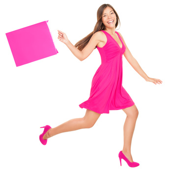 Happy shopping woman in pink running with shopping bags. Isolated on white background in full length.